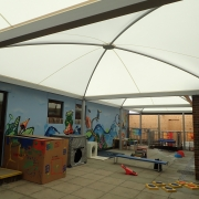 A picture of the outdoor classroom, showing the large canopy roof and the play equipment