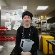 A smiling young woman holding jug in cafe kitchen