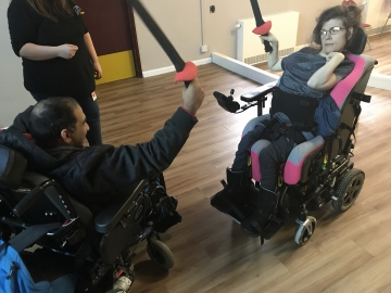 Two wheelchair users learning to fence