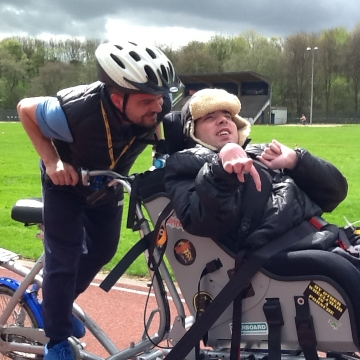 A participant and member of staff using an adaptive cycle